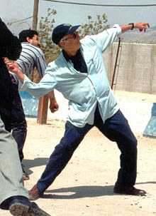 """O escritor palestino Edward Said, em gesto simbólico e """"progressista"""", atira pedras nos """"inimigos"""" israelenses."""