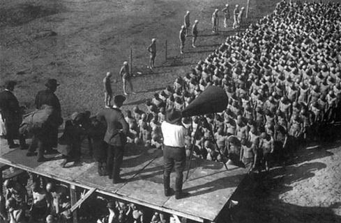 Em still de Horst von Harbou, Fritz Lang dirige uma massa de figurantes para a cena dos escravos sacrificados ao Moloch.